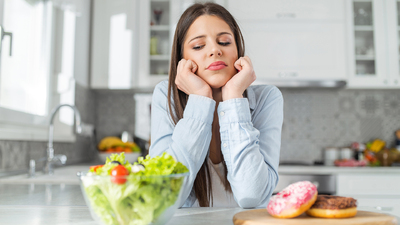 Woman choosing between doughnuts and salad