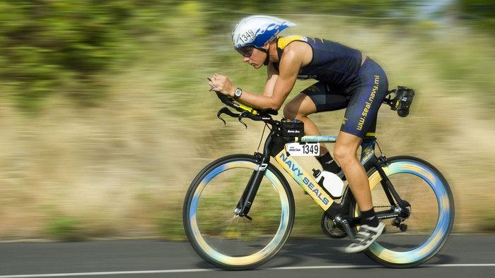 Triathlete cycling while using aero bars