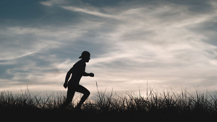 Silhouette of a man running through a field