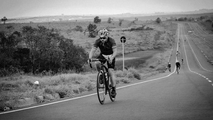 Triathlete cycling on a long road.
